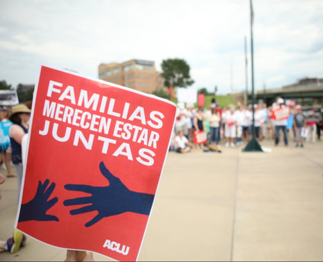 A Spanish 'Families Belong Together' sign in front of a crowd at a rally.